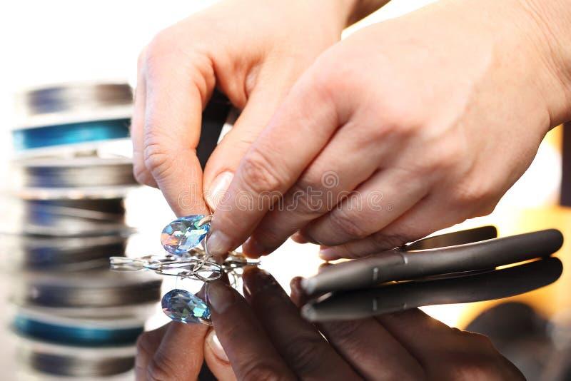 El joyero realiza el collar con los cristales foto de archivo libre de regalías