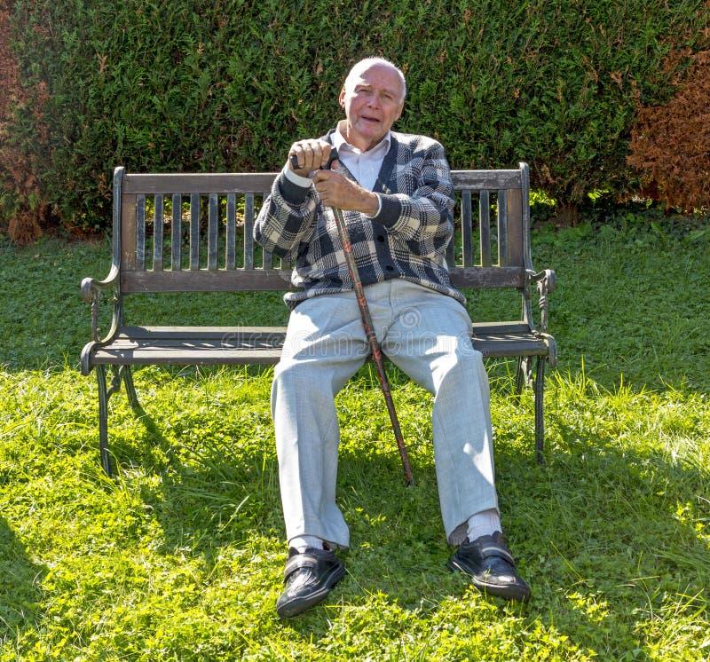 El jubilado goza el sentarse en un banco en su jardín imágenes de archivo libres de regalías