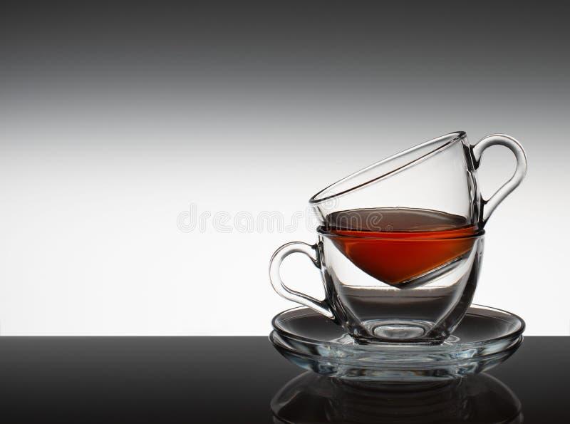 El juego de té consiste en dos bol de vidrio y un platillo en un fondo gris imágenes de archivo libres de regalías