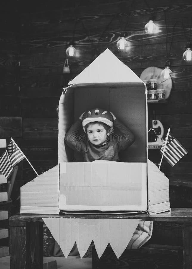 El juego del muchacho con el cohete, cosmonauta se sienta en los E.E.U.U. alcanza gran altura rápida y súbitamente hecho fuera de fotografía de archivo