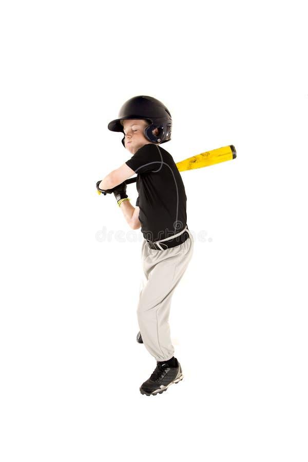 El jugador de béisbol joven del muchacho que balancea en la echada con el suyo observa cerrado foto de archivo libre de regalías