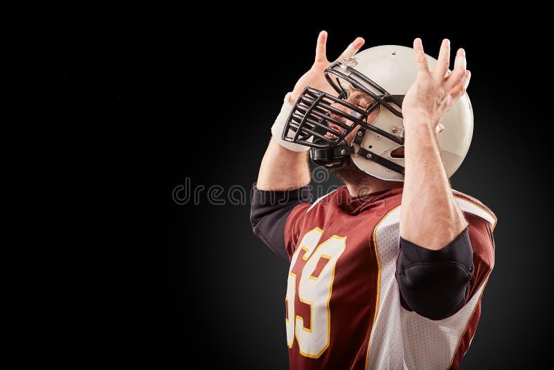 El jugador de fútbol americano aislado disfruta en la victoria en fondo negro imagen de archivo