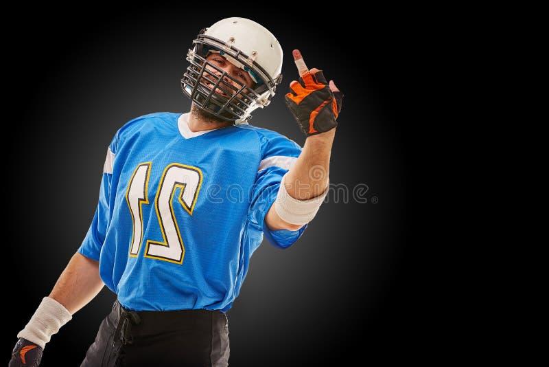 El jugador de fútbol americano en uniforme muestra cogida de la mano Fútbol americano, espacio de la copia, fondo negro imágenes de archivo libres de regalías