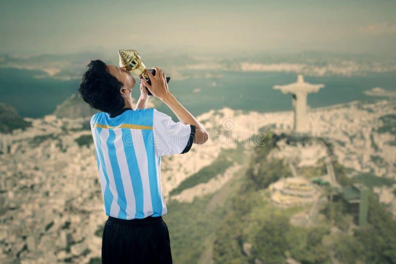 El jugador de fútbol celebra ganar con un trofeo 1 fotografía de archivo libre de regalías