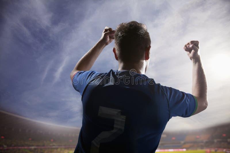 El jugador de fútbol con los brazos aumentó animar, el estadio con el cielo y las nubes imagenes de archivo