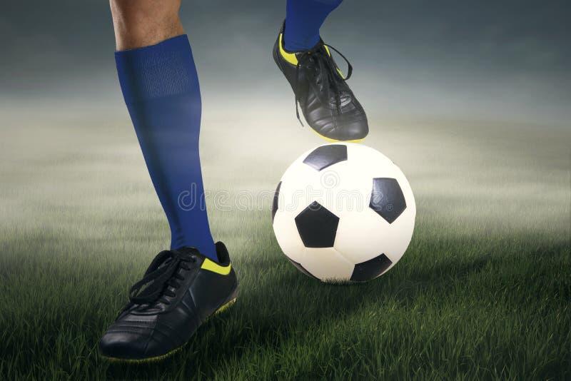 El jugador de fútbol de los pies con una bola imagenes de archivo