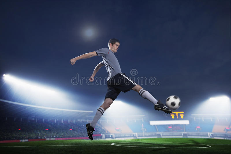 El jugador de fútbol en el mediados de aire que golpea el balón de fútbol con el pie, estadio se enciende en la noche en fondo fotografía de archivo libre de regalías