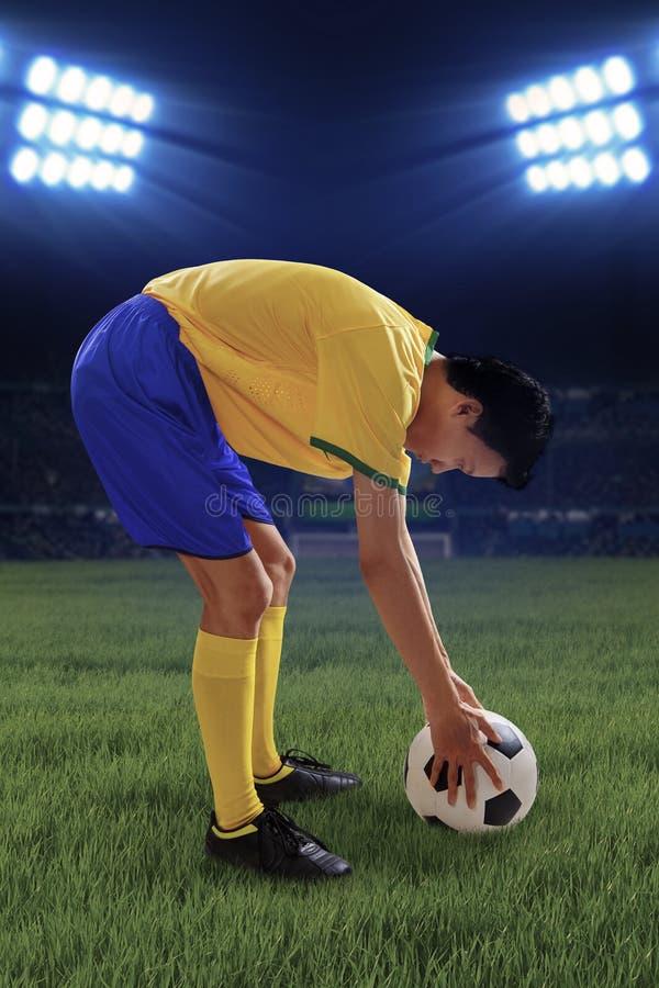 El jugador de fútbol puso la bola en el campo foto de archivo