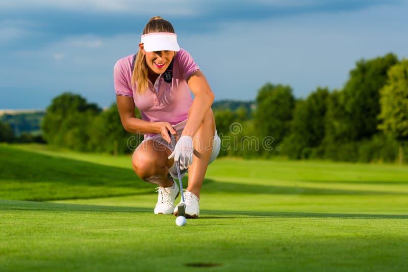 El Jugador De Golf Femenino Joven En El Curso Que Apuntaba Para Ella Puso Fotografía de archivo