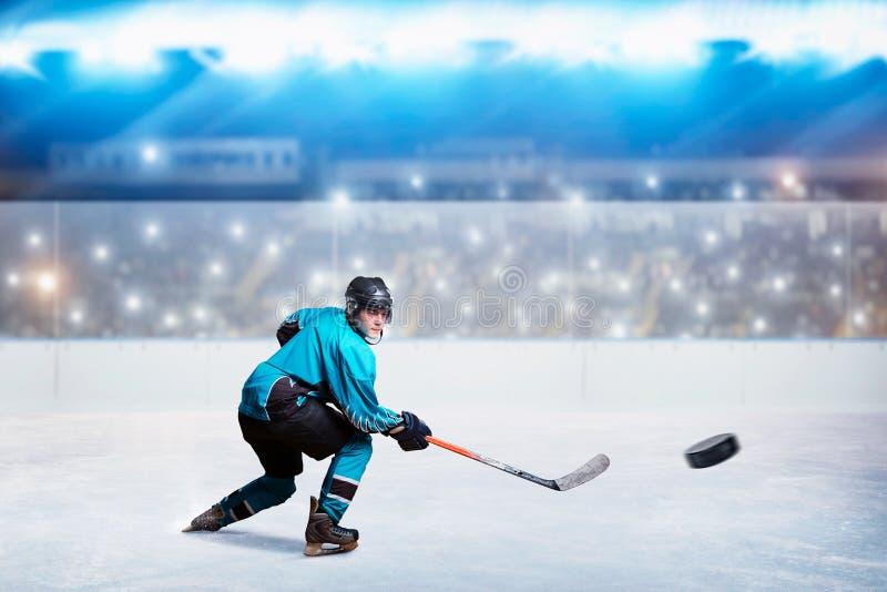 El jugador de hockey con el palillo y el duende malicioso hace un tiro fotografía de archivo libre de regalías