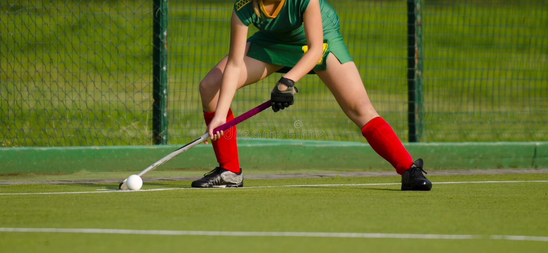 El jugador de hockey hierba, alista para pasar la bola a un compañero del equipo imagen de archivo libre de regalías