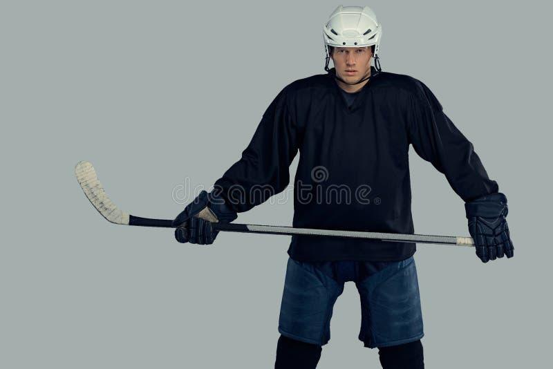 El jugador de hockey que lleva el engranaje protector negro y el casco blanco celebra un palillo de hockey en un fondo gris imagen de archivo libre de regalías
