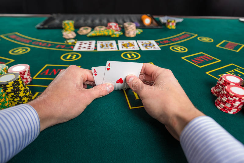 El jugador de póker masculino que levanta las esquinas de dos tarjetas aces fotos de archivo