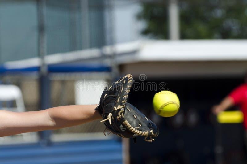 El jugador de softball alcanza hacia fuera para coger la bola imagenes de archivo