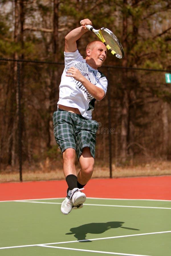 El jugador de tenis de sexo masculino sigue a través en el salto del tiro de arriba foto de archivo libre de regalías
