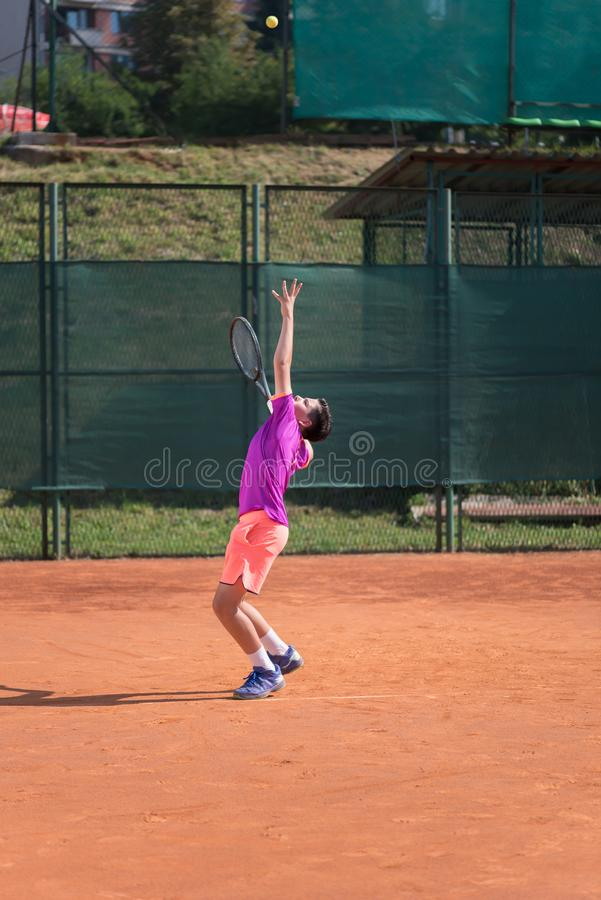 El jugador de tenis joven se prepara para servir la bola fotografía de archivo