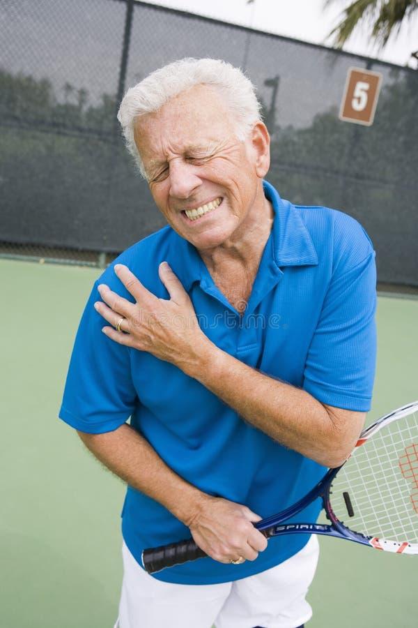 El jugador de tenis mayor hiere el hombro derecho imagen de archivo libre de regalías