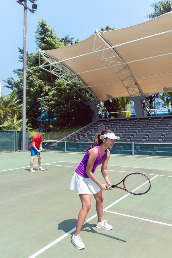 El jugador de tenis de sexo femenino confiado que espera para golpear la bola durante hace imagen de archivo