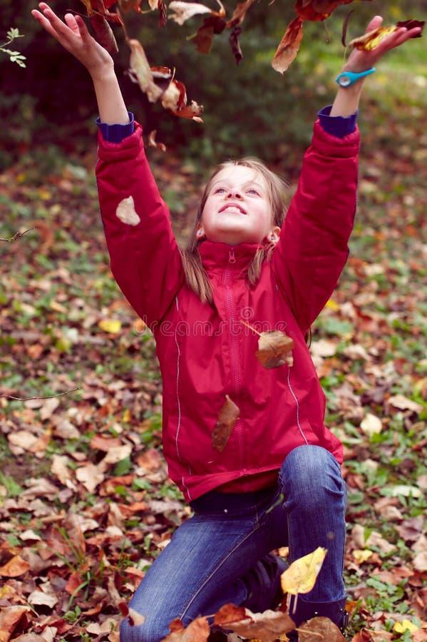 El jugar adolescente de la muchacha con las hojas de otoño para arriba en el aire fotografía de archivo