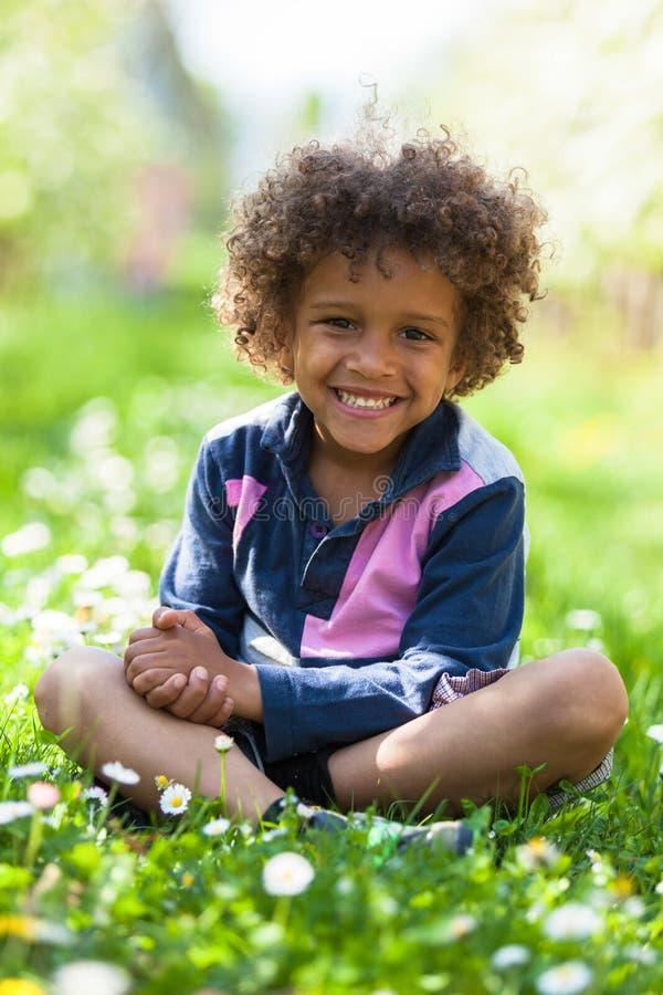 El jugar afroamericano lindo del niño pequeño al aire libre foto de archivo libre de regalías