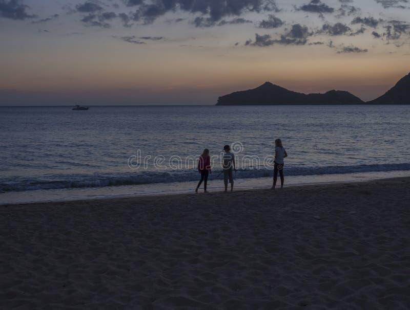 El jugar childern tres en la playa de Agios Georgios Pagon de la orilla de mar en la isla de Corfú, Grecia en la hora azul despué imagen de archivo
