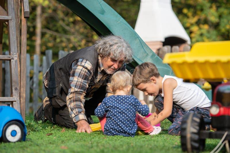 El jugar de abuelo con el nieto y la nieta afuera en i foto de archivo