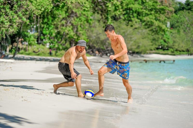 El jugar de los amigos footbal en la playa tropical soleada fotos de archivo