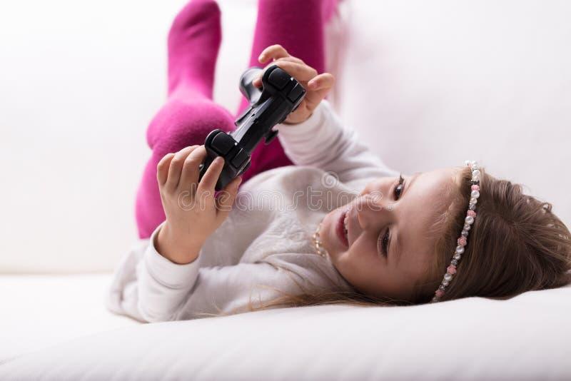 El jugar de mentira de la niña con un regulador del juego fotos de archivo libres de regalías