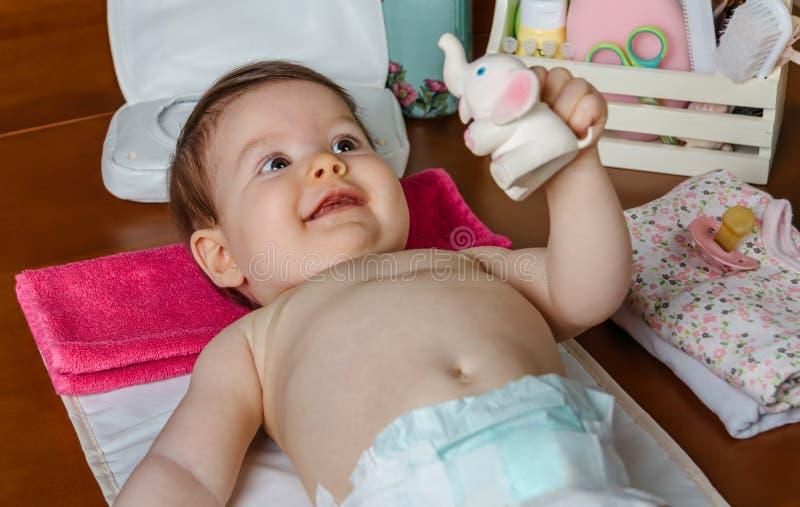 El jugar de mentira del bebé con un juguete de goma fotos de archivo libres de regalías