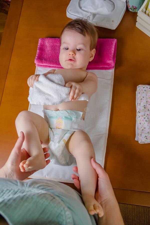 El jugar de mentira del bebé con una pequeña toalla imagen de archivo libre de regalías
