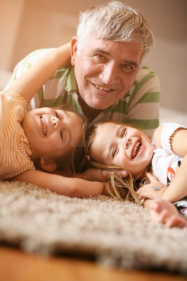 El jugar del abuelo y de las nietas Diversión y sonrisa fotos de archivo libres de regalías