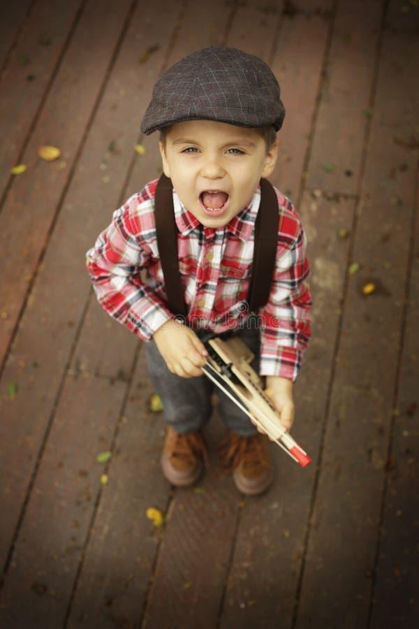 El jugar del niño pequeño al aire libre con un arma de madera del juguete imagenes de archivo