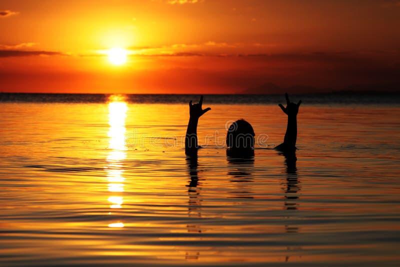 El jugar en el agua en la puesta del sol imagen de archivo libre de regalías