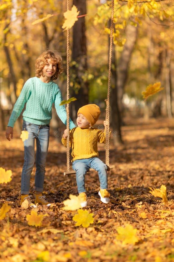 El jugar feliz de los niños al aire libre en parque del otoño imagenes de archivo