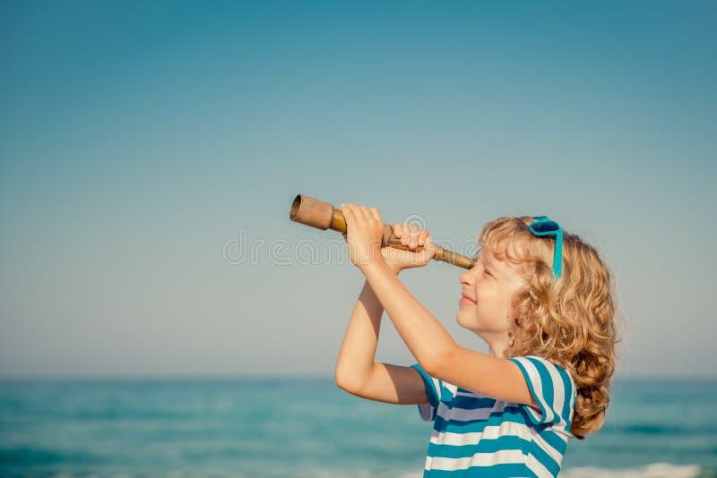 El jugar feliz del niño al aire libre contra el mar y el cielo imagenes de archivo