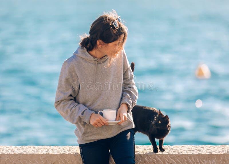El jugar femenino joven con el gato negro cerca del mar fotografía de archivo