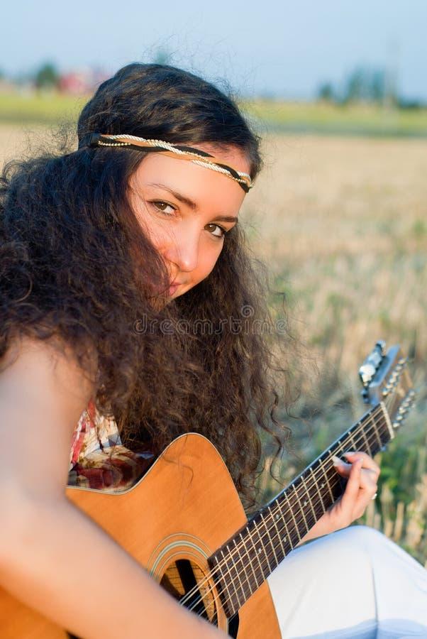 El jugar hermoso de la mujer gitar foto de archivo