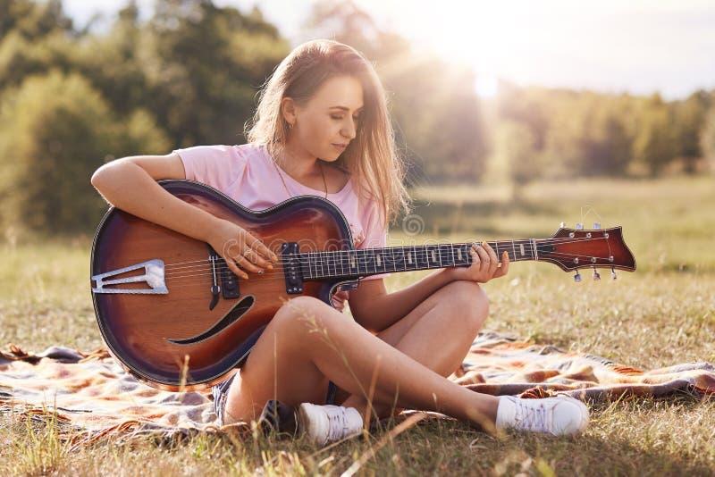 El jugar hermoso de la mujer joven gitar en prado, tiene pelo rubio recto, miradas concentradas en el insrtument musical, el llev fotos de archivo