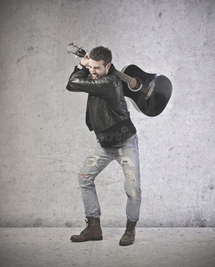 El jugar hermoso enojado de la guitarra foto de archivo