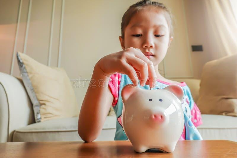 El jugar lindo de la niña recoge el dinero con un tarro de ahorro rosado del cerdo imagen de archivo libre de regalías
