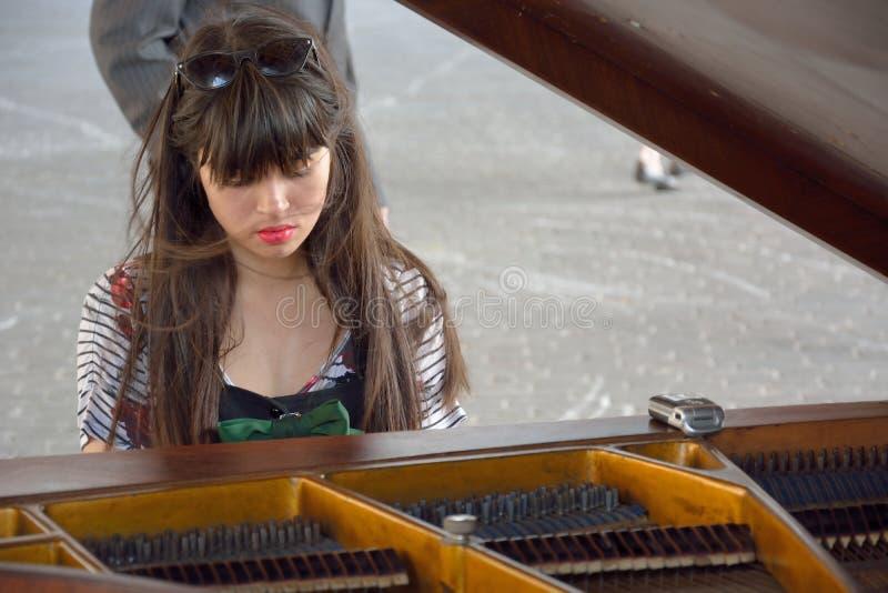 El jugar muy hermoso de la mujer joven se centró en el piano público fotos de archivo libres de regalías