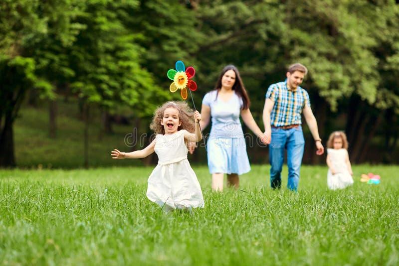 El jugar que camina de la familia feliz en el parque fotografía de archivo