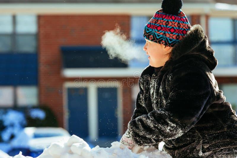 El jugar que lleva de risa feliz de la niña y funcionamiento en un parque nevoso hermoso del invierno imagen de archivo libre de regalías