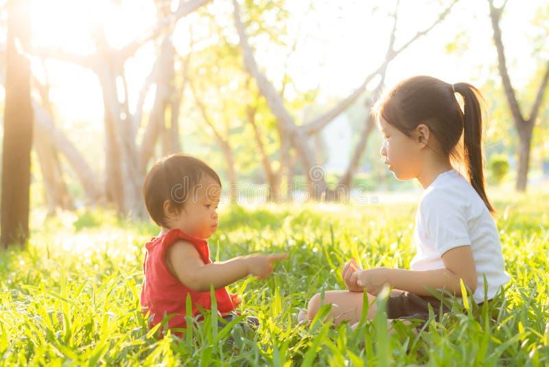 El jugar que se sienta del ni?o asi?tico joven hermoso en verano en el parque con goza y alegre en hierba verde fotografía de archivo libre de regalías