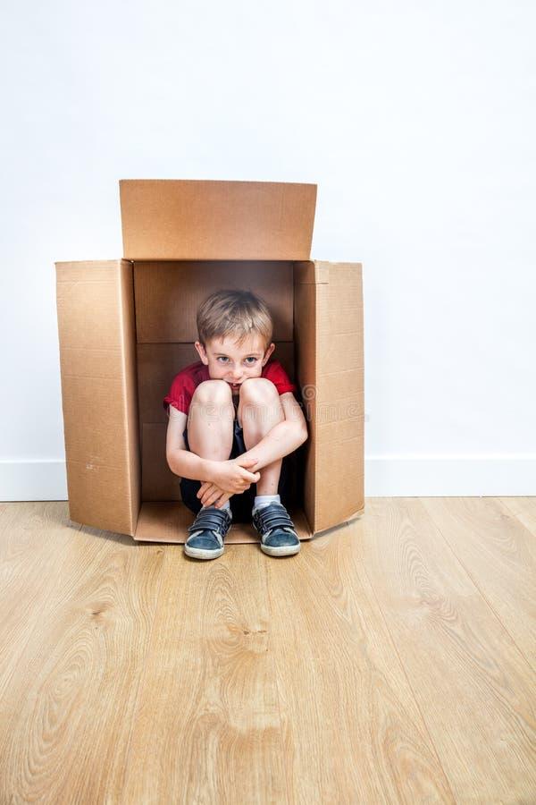 El jugar sonriente del niño, sentándose en la caja que juega para el día móvil imagen de archivo libre de regalías