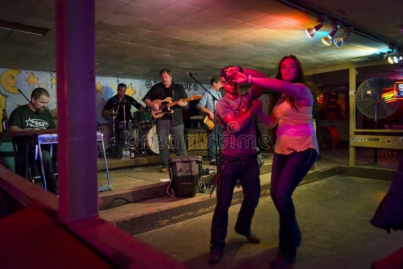 El jugar y gente de la banda de la música country que bailan en el pasillo de danza quebrado del rayo en Austin, Tejas foto de archivo libre de regalías