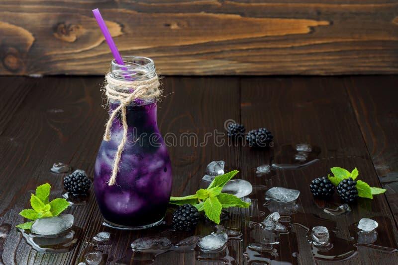 El jugo de restauración de la zarzamora en eco del vintage diseña la botella en la tabla de madera oscura rústica Bebida fría de  imagenes de archivo