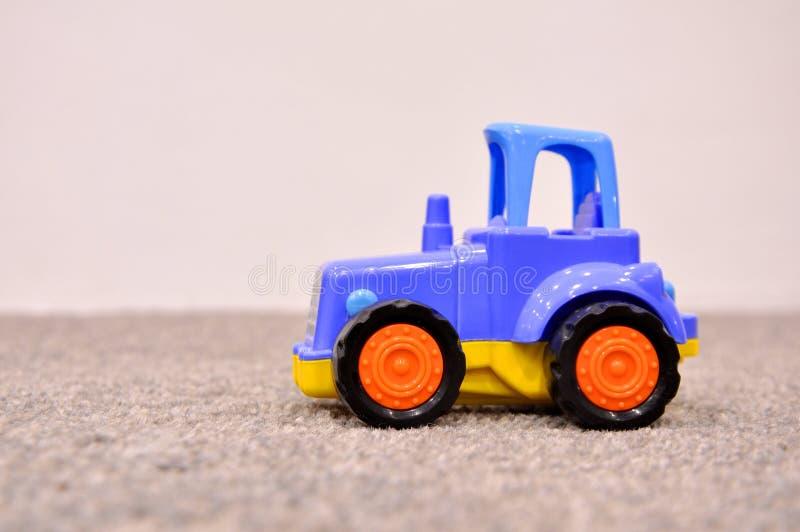 El juguete de los niños, tractor azul fotografía de archivo