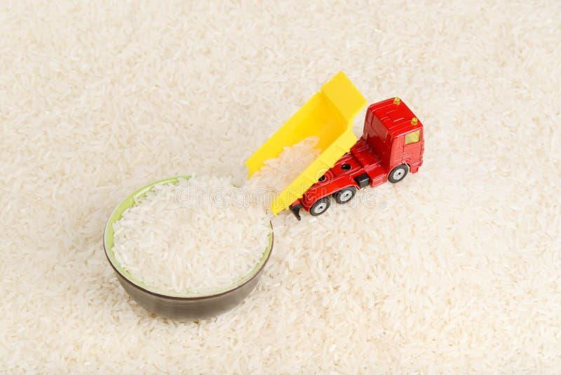 El juguete del camión volquete descarga granos del arroz para platear imagenes de archivo
