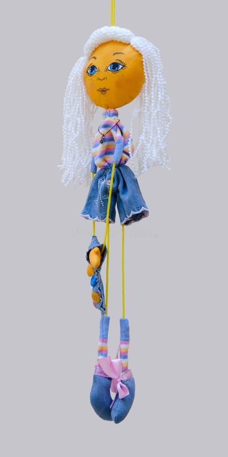 El juguete hecho a mano de la muñeca aisló a la muchacha alegre rubia fina en dre de los vaqueros imagen de archivo